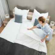 housekeeper making a bed