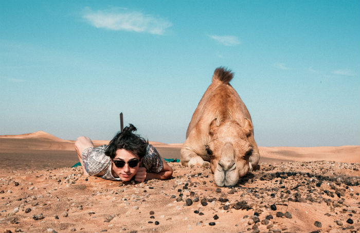 camel and man lying on the desert sand