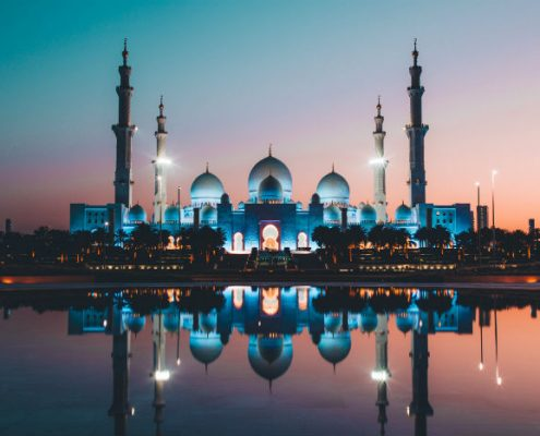 Middle East palace lit up in blue and white at sunset