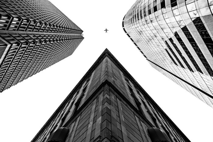 plane in the sky between buildings