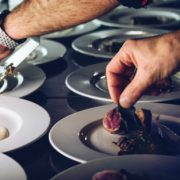 hands placing food on plate