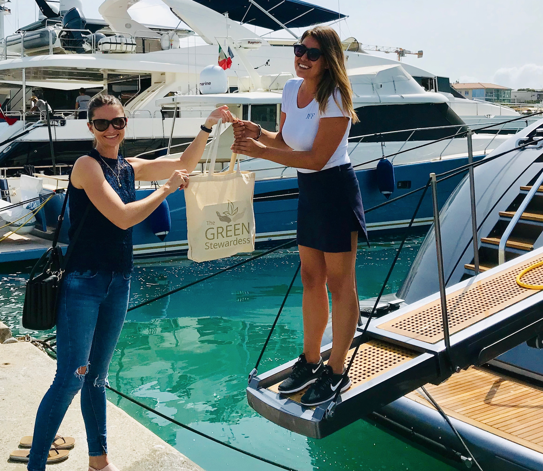 The Green Stewardess and a friend holding up a tote bag while standing at the back of a yacht