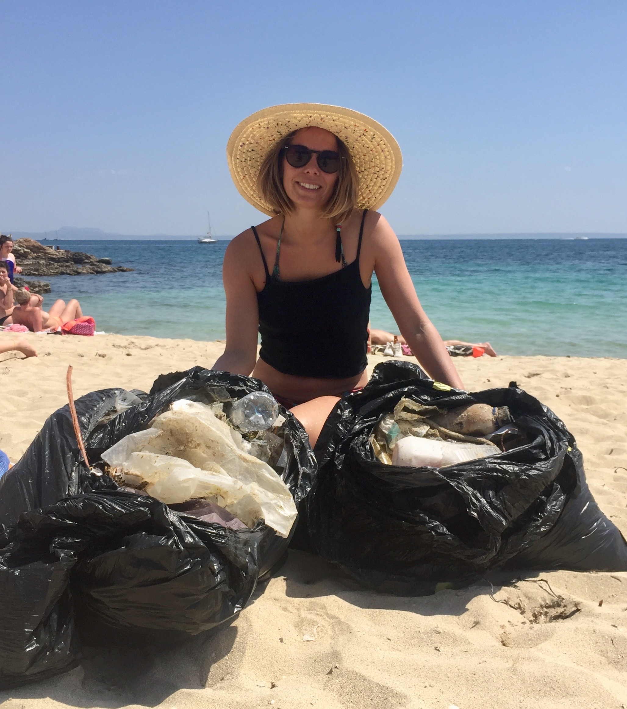 Girl on a beach with full rubbish bags