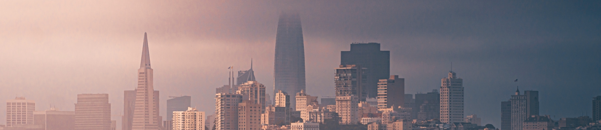 A cloudy city skyline at dusk