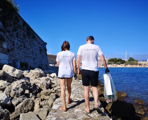 Two people walking along a small sea wall next to the sea
