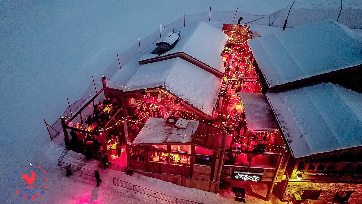 View from above of a bar in the Alps with snow on the roof and around the sides