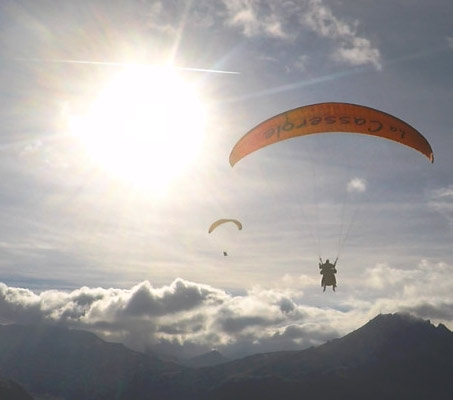 Two people paragliding above the clouds and mountains in the Alps, France