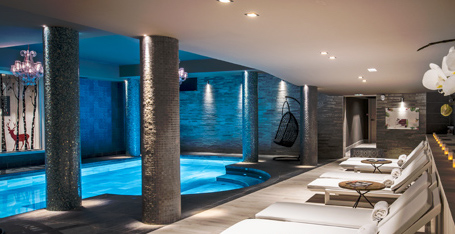 Blue-lit indoor pool with lounger beds around the edge