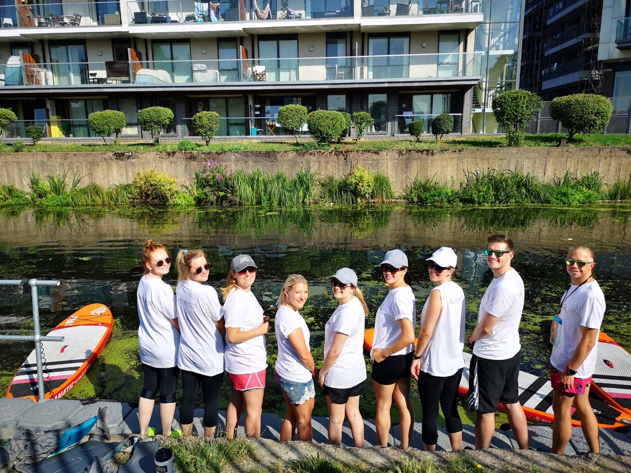 9 of the Silver Swan team standing on the edge of the canal at Limehouse London with paddle-boards in the water