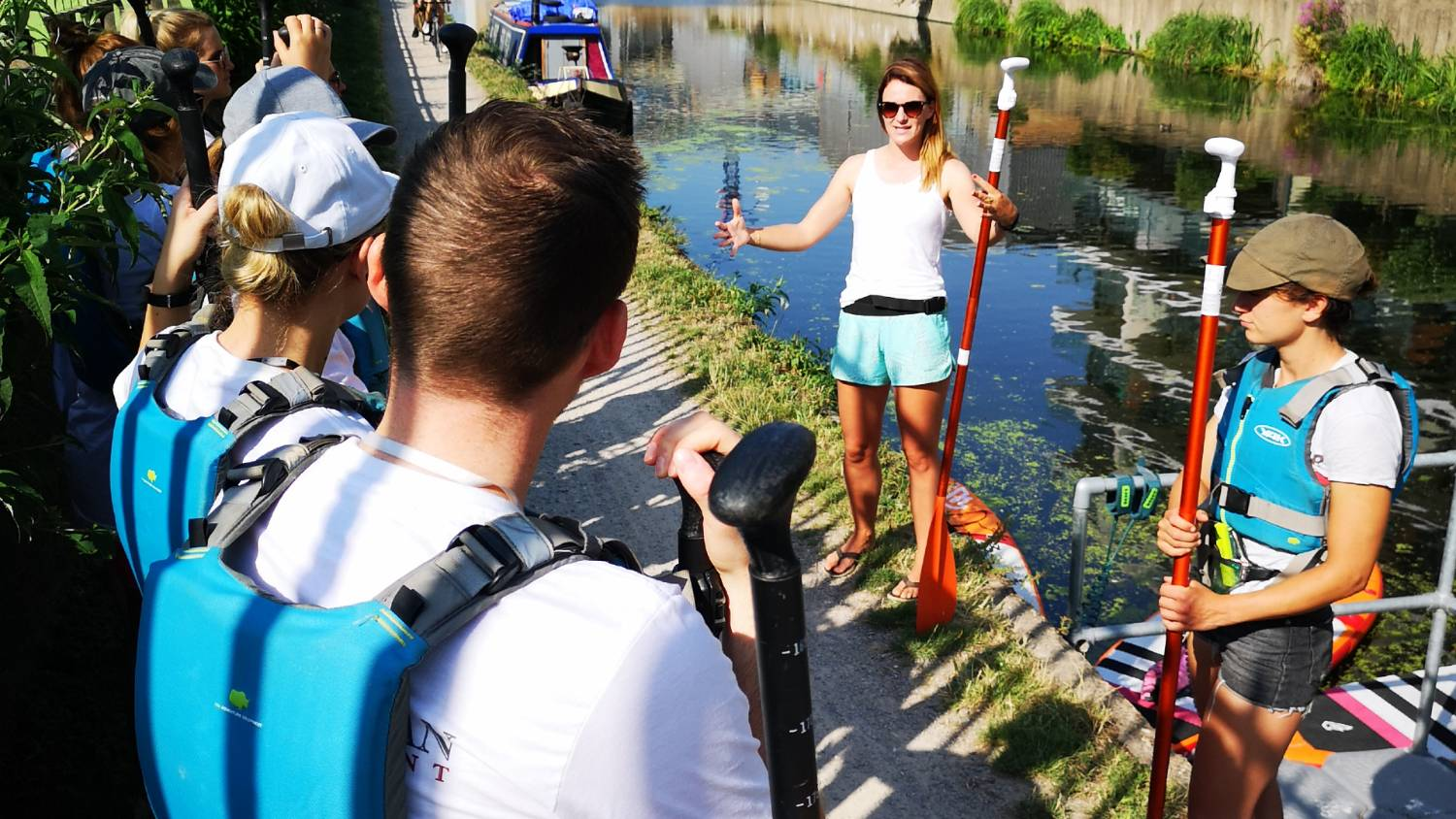 Group of people being briefed on the edge of the canal before a paddle board clean up with Plastic Patrol