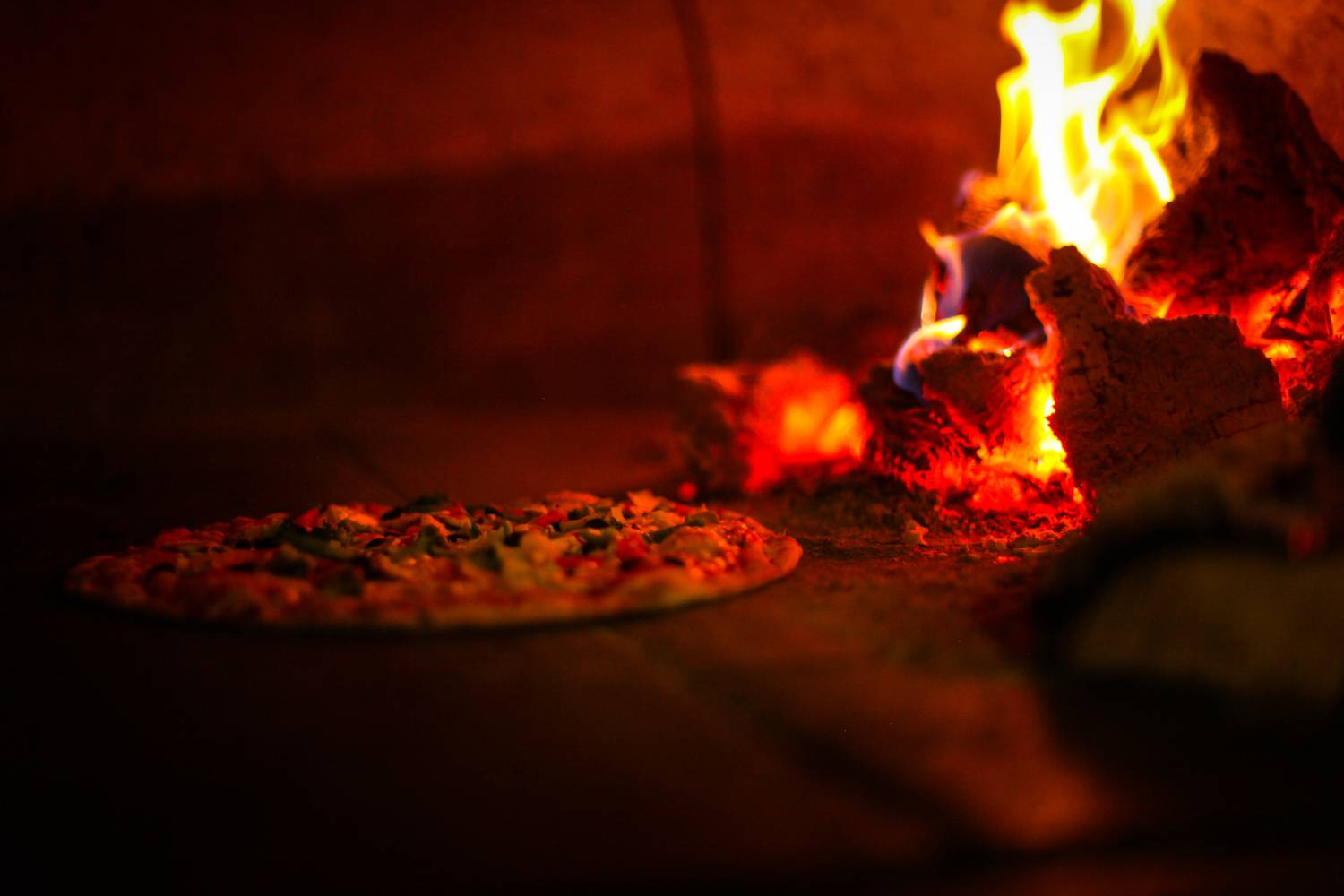 Pizza in a pizza oven with fire next to it