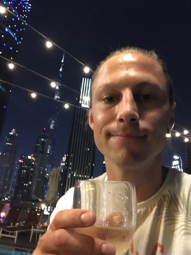 Guy taking a selfie holding a glass of wine