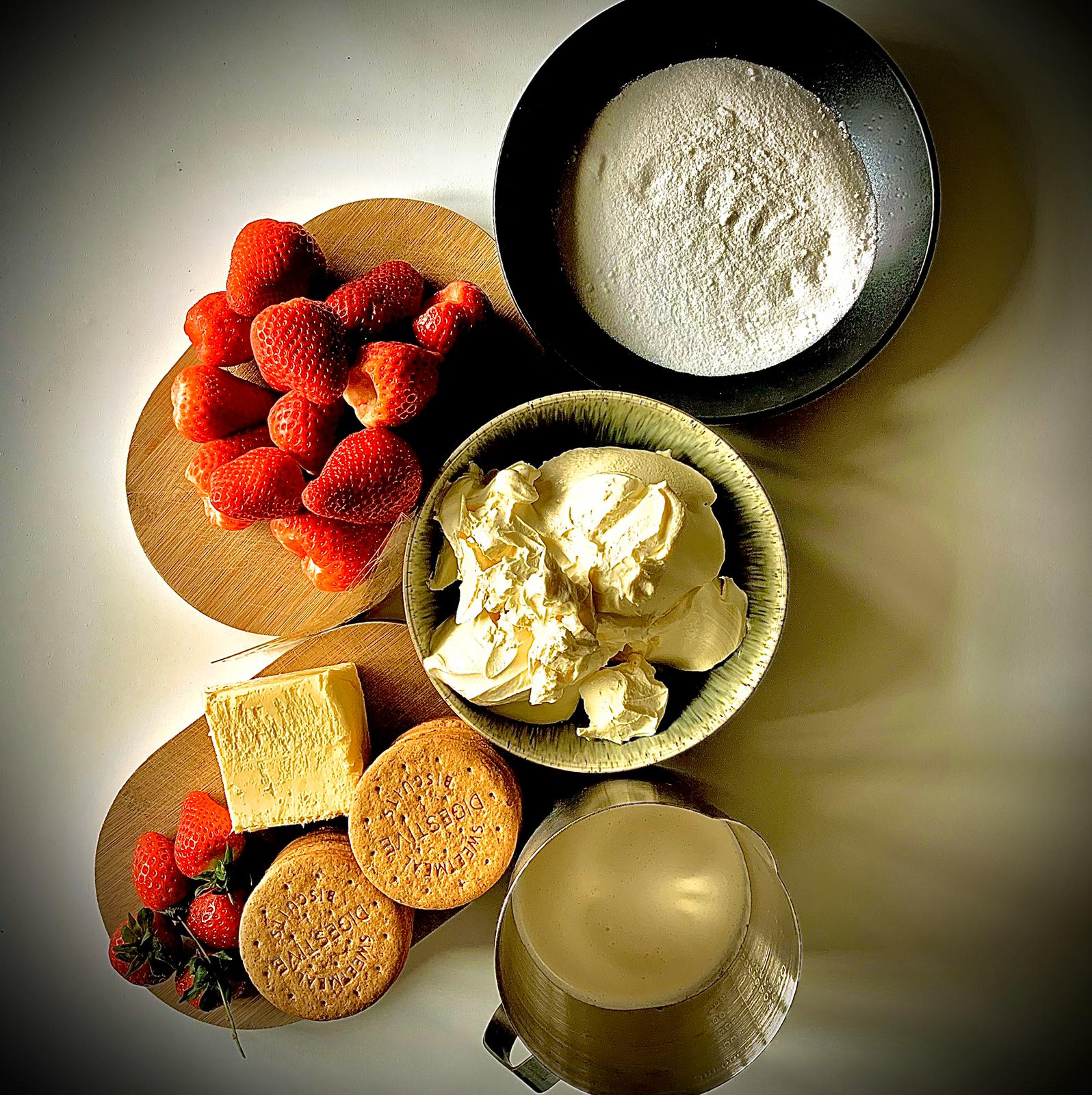Aerial picture of strawberry cheesecake ingredients - strawberries, cream, butter, sugar and biscuits
