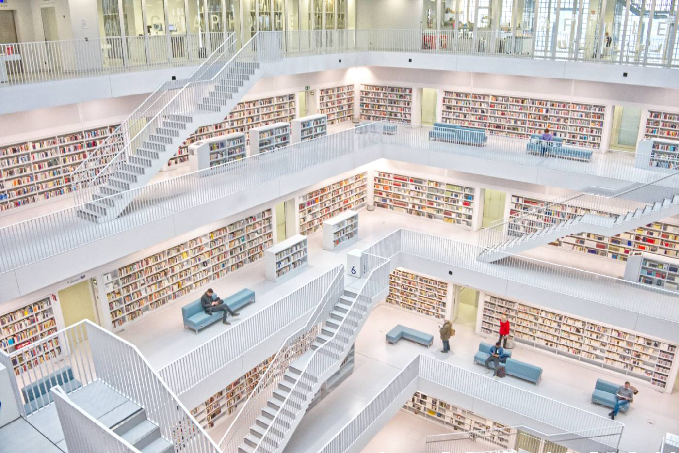 A huge library with white balconies and stairways, set across 5 floors