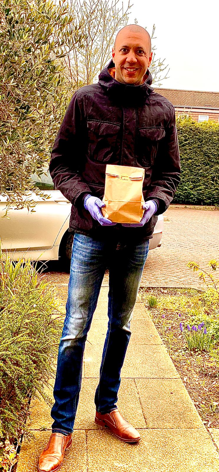 Chef, Gary Martin, standing outside a house with a meal about to be delivered