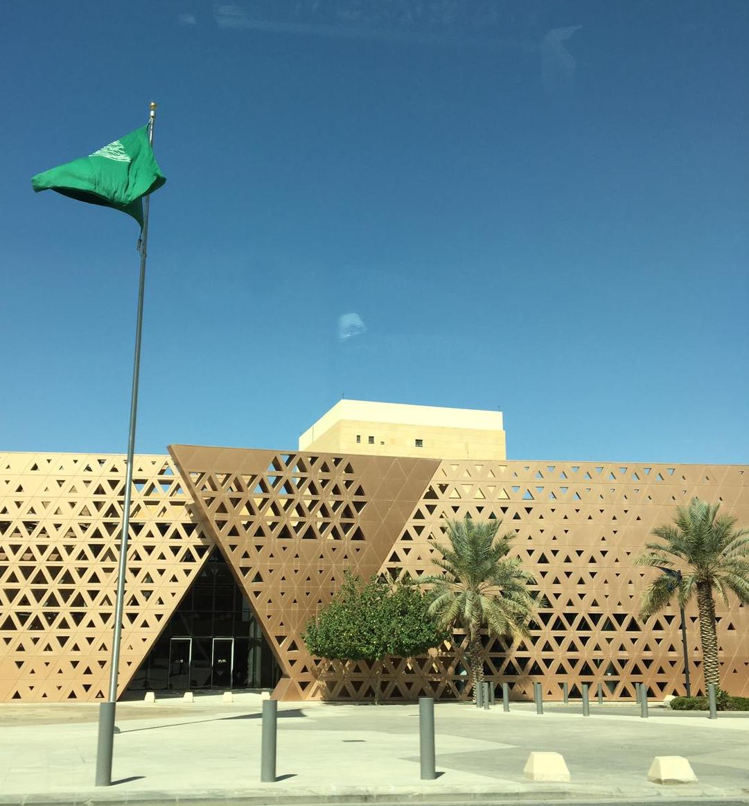 Beautiful architecture in Riyadh, Saudi Arabia. A building made up of triangle shapes in gold metal, with the national flag flown above the roof.