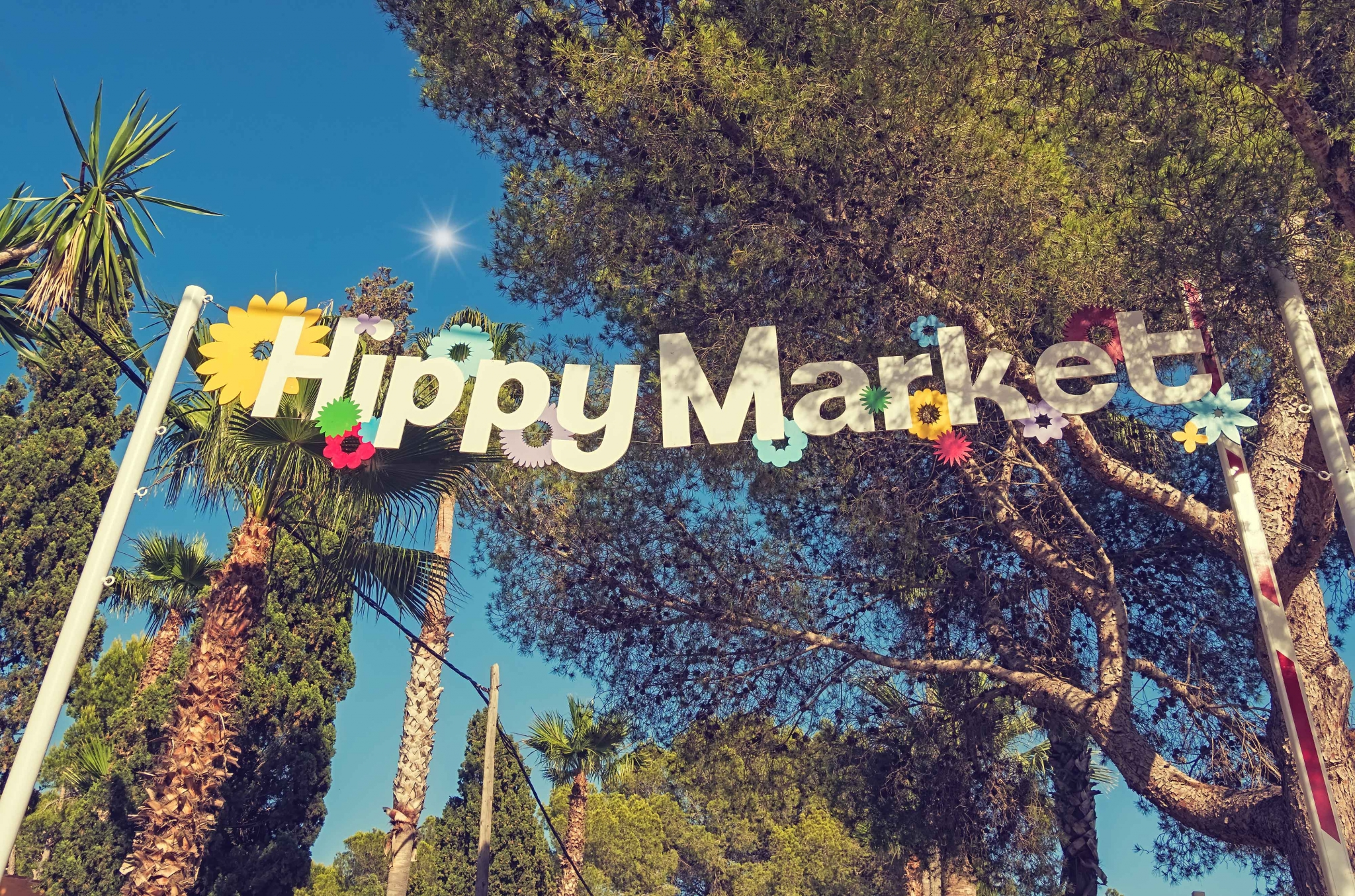 Entrance to a market with a big sign saying 'Hippy Market', in Ibiza