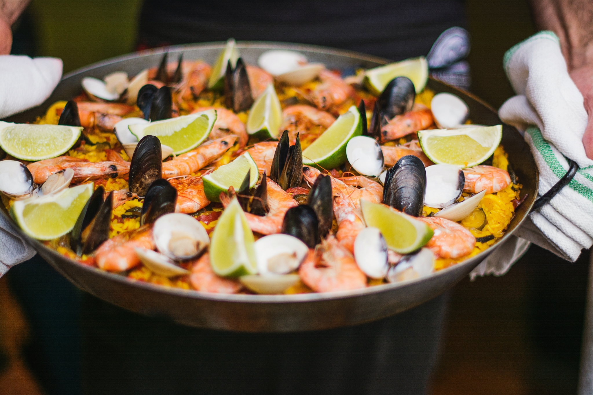A dish of seafood paella with clams and lime wedges on top