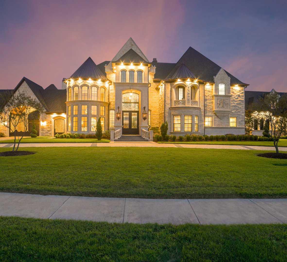 A mansion lit up in the dusk